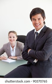 Portrait of a businessman posing while his colleague is working in an office