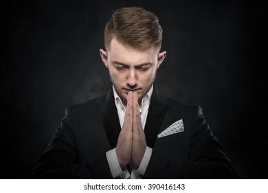 Portrait of businessman praying or thinking over dark background.