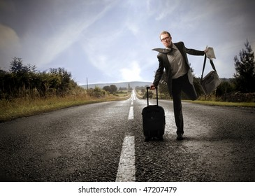 Portrait of a businessman running on a countryside road and carrying some bags