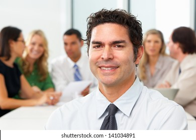 Portrait Of Businessman Sitting At Boardroom Table