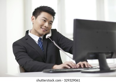 Portrait of businessman sitting by computer,talking on phone at desk in office