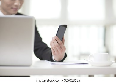 Portrait of businessman sitting at desk and looking at cell phone,close-up
