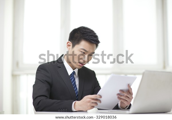 Portrait of businessman sitting at desk and looking at documents