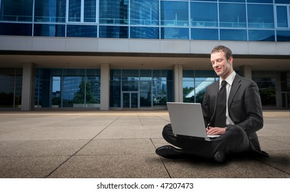 Portrait of a businessman sitting in front of a building and using a laptop