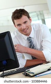 Portrait of businessman sitting at his desk in office