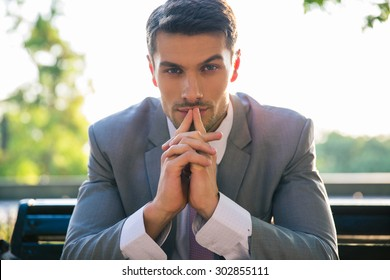 Portrait of a businessman sitting on the bench outdoors and thinking