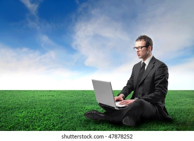 Portrait of a businessman sitting on a green meadow and using a laptop