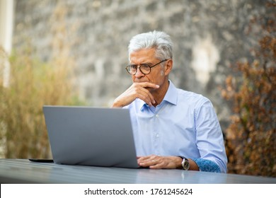 Portrait businessman sitting outside working with laptop