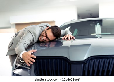 Portrait of a businessman smiling joyfully and embracing a new car at the dealership showroom