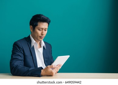 Portrait of businessman smiling and using pad at desktop against of blue wall. Vintage filtered image.