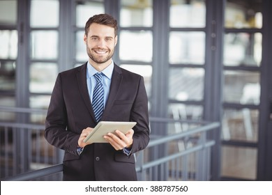 Portrait of businessman smiling while using digital tablet in office