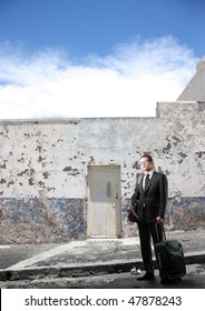 Portrait of a businessman standing in front of an ancient building and carrying a suitcase