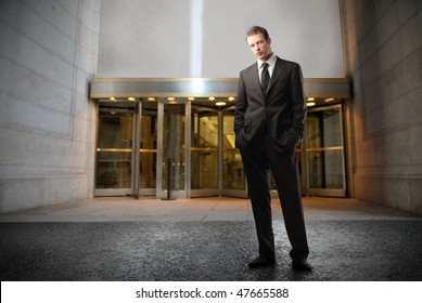 Portrait of a businessman standing in front of the entrance of a building