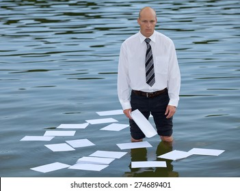 Portrait of businessman standing in lake with papers floating on water