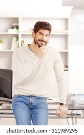 Portrait of businessman standing at office in front of computer and thinking. Young creative wearing casual clothing.