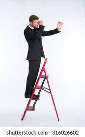 Portrait of businessman standing on the ladder and using telescope isolated on white. Man in suit dreaming to see the business future reality.
