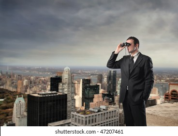 Portrait of a businessman standing on the top of a skyscraper and using a pair of binoculars