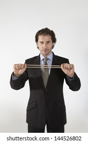 Portrait of a businessman stretching rubber band on gray background