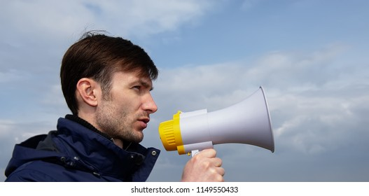 Portrait of a businessman with a stubble on his face screams over a megaphone. Horizontal photo banner for website header design with space for text.