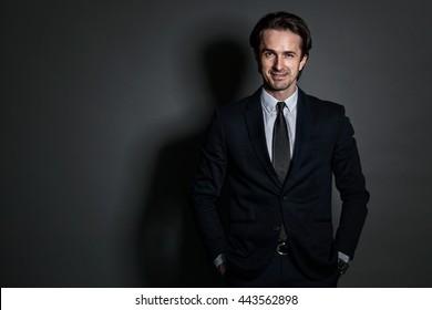Portrait of businessman in suit on dark background