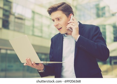 Portrait of businessman talking on the phone and looking at the laptop