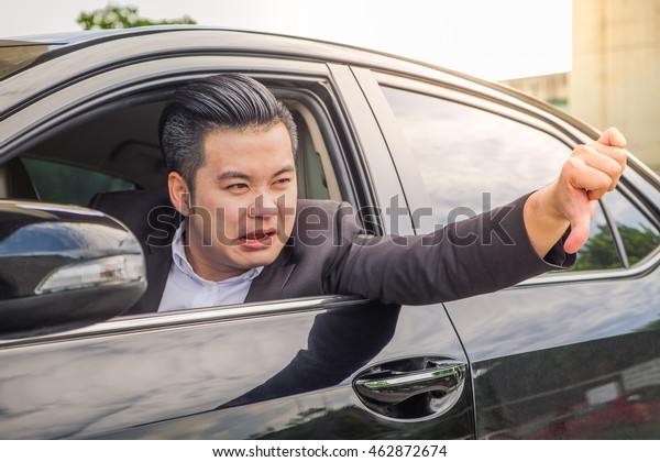 Portrait of businessman unhappy using smartphone calling for assistance with his car broken down by the roadside. Young Asian man disappointed while driving automobile commute to work on the road trip
