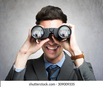 Portrait of a businessman using binoculars, people portraits reflected in the lens