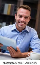 Portrait of businessman using digital tablet at restaurant