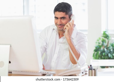 Portrait of businessman using landline phone while working on computer at desk in office