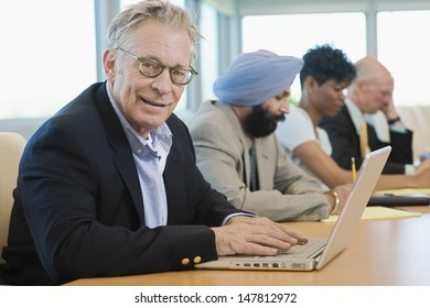Portrait of a businessman using laptop besides multiethnic colleagues in conference room