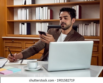 Portrait of businessman using smartphone at work