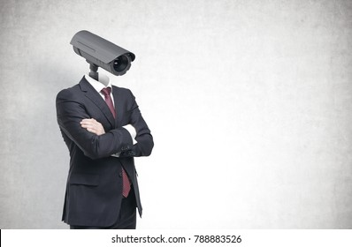 Portrait of a businessman wearing a suit and standing with crossed arms. His head is a CCTV camera. Concept of surveillance and monitoring. A concrete wall background. Mock up