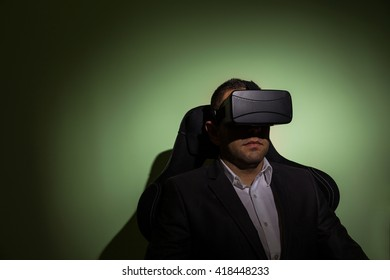 portrait of a businessman wearing virtual reality glasses against a green background