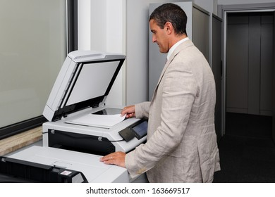 Portrait of a businessman who makes a photocopy as a concept of office life