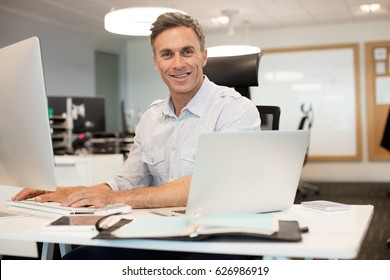Portrait of businessman working on computer at desk in office