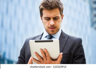 Portrait of a businessman working on his tablet