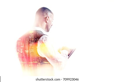 Portrait of businessman working on a tablet pc rear view double exposure