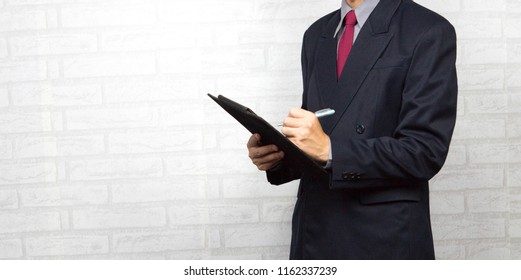 Portrait of Businessman Writing and Making Notes on Black Clipboard. Isolated on White Wall Background. Business Concept.