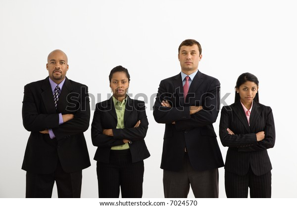 Portrait of businessmen and businesswomen standing with arms crossed looking serious.
