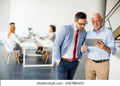 Portrait of businessmen with digital tablet in office
