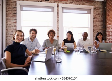 Portrait Of Businesspeople Sitting Around Boardroom Table