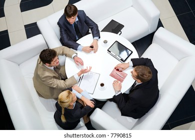 Portrait of businesspeople sitting around at the table and discussing an important questions