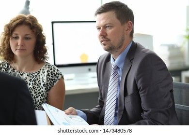 Portrait of businesspeople sitting in conference room and discussing important business project with colleagues. Biz meeting and negotiations concept. Blurred background