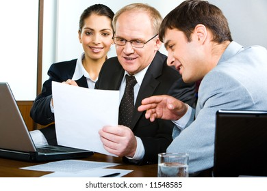 Portrait of businessteam looking at new business plan held by their senior boss and discussing it