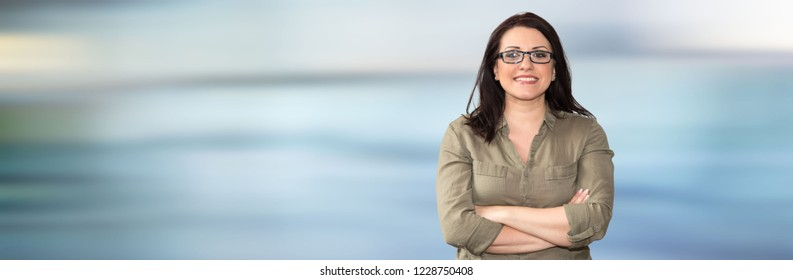 Portrait of businesswoman with arms crossed on blurred background