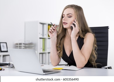 Portrait of a businesswoman in a black dress on a phone. She is sitting in a white office and looking at her laptop screen.