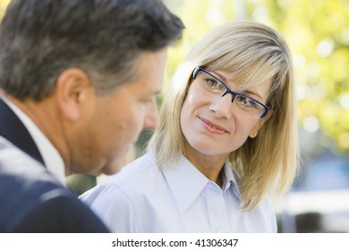 Portrait of a Businesswoman and a Businessman Sitting on a Bench Outdoors
