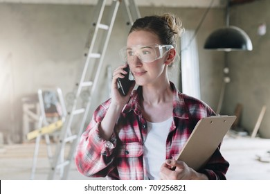 Portrait of businesswoman engineer, architect, designer.Girl standing,talking on cell phone and holding clipboard.Construction, phone cellrepair, redevelopment, project approval.In  background repair.