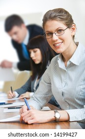 Portrait of businesswoman with glasses writing something on the paper looking at camera during seminar