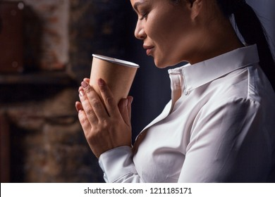 Portrait of businesswoman having coffee. Isolated on dark background.